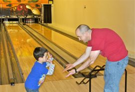 Man_and_boy_high-fiving_each_other_(Strike_Zone_Bowling_Center,_Camp_Humphreys)
